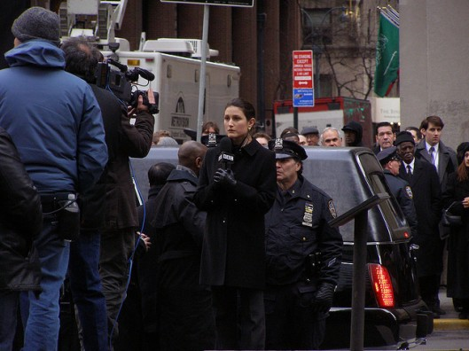 An actress portrays a reporter during filming in NYC